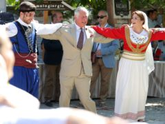 The Prince of Wales tries his hand at Greek dancing during a walkabout in Archanes, Crete (Andrew Matthews/PA)