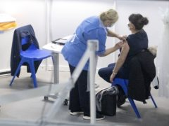 A nurse administers a coronavirus vaccine to a health and care staff member at the NHS Louisa Jordan (Jane Barlow/PA)