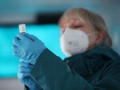 An NHS nurse prepares a dose of the Oxford-AstraZeneca Covid-19 vaccine (PA)
