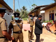 Police officers outside a house where a nine-year-old girl was canned to death in Delgoda, Sri Lanka (AP/Sudath Pubudu Keerthi)