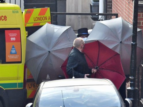 Staff use umbrellas to shield someone getting into an ambulance outside the rear of the King Edward VII Hospital in London (Dominic Lipinski/PA)