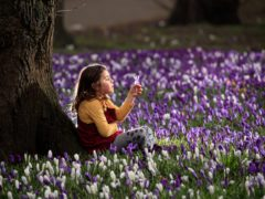 Sophia Gibson holds a crocus on the first day of meteorological spring at Kirkstall Abbey Park in Leeds, West Yorkshire (Danny Lawson/PA)