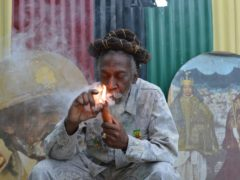 """Bunny Wailer smokes a pipe stuffed with marijuana during a """"reasoning"""" session in a yard in Kingston, Jamaica. Wailer, a reggae luminary who was the last surviving member of the legendary group The Wailers, died on Tuesday, March 2, 2021, in his native Jamaica, according to his manager. He was 73. (AP Photo/David McFadden, File)"""