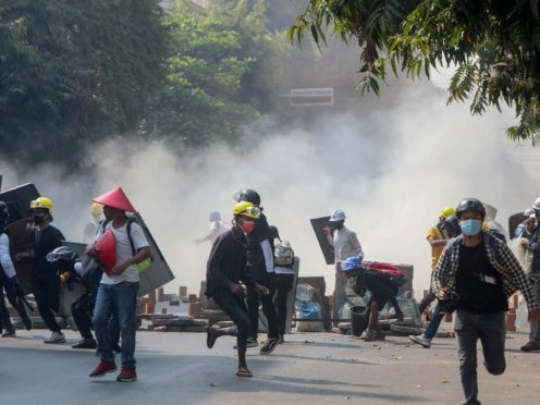 Anti-coup protesters run from tear gas and charging riot police and soldiers in Mandalay in Myanmar (AP)