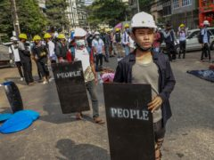 Anti-coup protesters with makeshift shields stand in Yangon (AP)