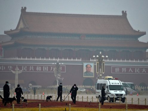 Police officers use sniffer dogs to check on Tiananmen Square before the opening session of China's National People's Congress on Friday. China's exports surged more than 60% in the first two months of the year compared with the same period of last year (Ng Han Guan/AP)
