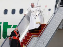 Pope Francis walks down the steps of an airplane as he arrives at Baghdad international airport, Iraq, Friday, March 5, 2021. Pope Francis heads to Iraq to urge the country's dwindling number of Christians to stay put and help rebuild the country after years of war and persecution, brushing aside the coronavirus pandemic and security concerns. (AP Photo/Andrew Medichini)