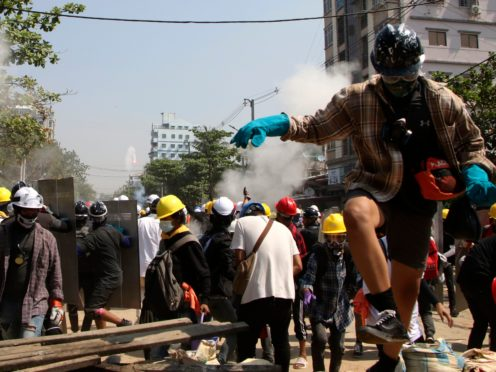 Protesters are dispersed as riot police fire tear gas behind a makeshift barricade in Yangon, Myanmar (AP)