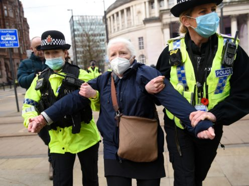 Police detain a woman after breaking up a protest in Manchester (PA)