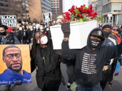 Cortez Rice, left, a friend of George Floyd, and Raj Sethuraju carried a mock coffin to mourn the death of George Floyd during a rally in Minneapolis, Minnesota (Jerry Holt/Star Tribune via AP)