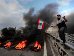 A protester waves a Lebanese flag near burning tyres (Hussein Malla/AP)