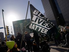 A demonstrator holds up a Black Lives Matter flag outside the Hennepin County Government Centre in Minneapolis, where the trial of former Minneapolis police officer Derek Chauvin began with jury selection (Jim Mon/AP)