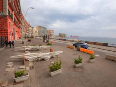 A police car patrols Naples' waterfront in Italy (Alessandro Pone/LaPresse via AP)
