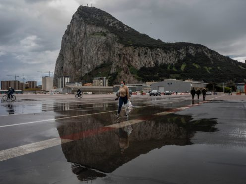 People cross the Gibraltar airport runway towards the border crossing with Spain, backdropped by the Gibraltar Rock, in Gibraltar (Bernat Armangue/AP)