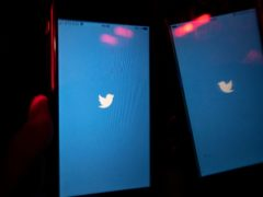 A mobile phone user turns on the Twitter application on his smartphone in Moscow, Russia (Alexander Zemlianichenko/AP)