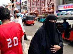 A Sri Lankan Muslim woman walks in a street of Colombo, Sri Lanka (Eranga Jayawardena/AP)