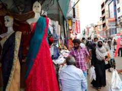 A Sri Lankan Muslim woman, right in black attire, walks in a busy street of Colombo, Sri Lanka (Eranga Jayawardena/AP)