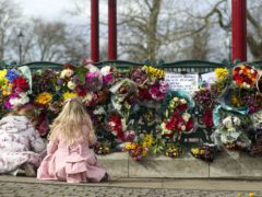 People leave floral tributes at the band stand in Clapham Common (Steve Parsons/PA)