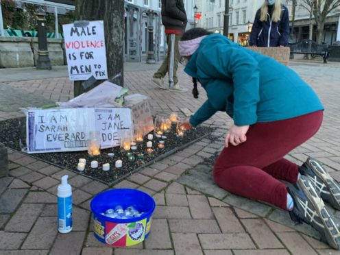 A woman lights a candle in Birmingham on March 13, 2021, after a vigil called following the death of Sarah Everard (Richard Vernalls/PA)