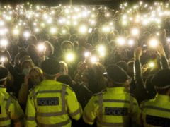 People in the crowd turn on their phone torches as they gather in Clapham Common, London, after the Reclaim These Streets vigil for Sarah Everard was officially cancelled (Victoria Jones/PA)