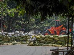 A man watches as soldiers use a bulldozer to remove sandbag barricades put in place by anti-coup protesters to protect them from security forces in Mandalay, Myanmar (STR/PA)