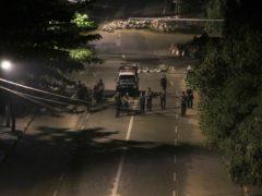 Armed police patrol a street in Yangon, Myanmar (AP)