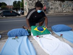 A demonstrator places a Brazil national flag on a mattress symbolising Covid-19 victims during a protest against the government's handling of the pandemic in Rio de Janeiro (AP Photo/Silvia Izquierdo/AP)