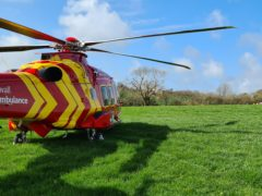 A Cornwall Air Ambulance helicopter in a field adjacent to where a Royal Navy Hawk jet crashed in woodland in Cornwall (Cornwall Air Ambulance/PA)