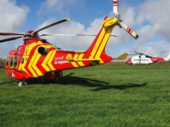 A Cornwall Air Ambulance helicopter alongside a Coastguard SAR helicopter in a field adjacent to where a Royal Navy Hawk jet crashed in woodland in Cornwall