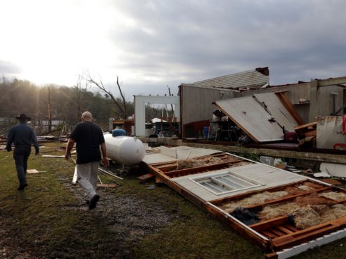 A neighbor walks with pastor Danny Poss to help remove valuables from the Ragan Chapel United Methodist church after a tornado touched down Friday, March 26, 2021 in Ohatchee, Ala. A tornado outbreak has ripped across the Deep South leaving paths of destruction. (AP Photo/Butch Dill)
