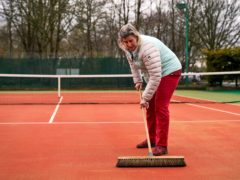 Ruth Williams, welfare officer and ladies captain brushes the courts at Wycombe House Tennis Club in Isleworth, London (John Walton/PA)