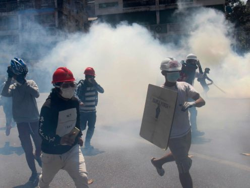 Anti-coup protesters run away from tear gas launched by security forces in Yangon (AP)