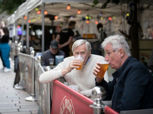 Members of the public enjoy their first drink in the beer garden at the Bier Halle, Glasgow (PA)
