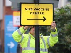 A Brent council worker hangs a direction sign to the Covid-19 vaccine centre at the Olympic Office Centre in Wembley (Yui Mok/PA)