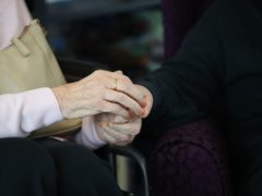 A care home resident holds hands with a visitor (Aaron Chown/PA)
