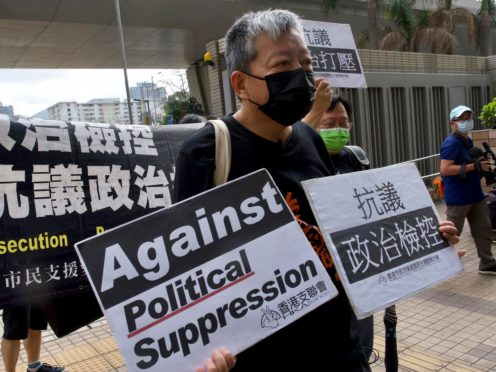 Pro-democracy activist Lee Cheuk-yan holds placards as he arrives at a court in Hong Kong where he was one of seven people convicted on charges of organising and participating in an unlawful assembly (Vincent Yu/AP)