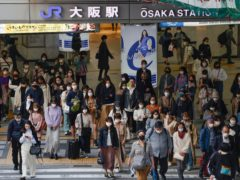 People wear face masks as they make their way in Osaka, western Japan (Kyodo News via AP)