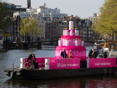 A huge inflatable pink cake with candles spouting rainbow flames glides through the Amsterdam canals as the Dutch capital celebrated the 20th anniversary of the world's first legal same-sex marriages (Peter Dejong/AP)