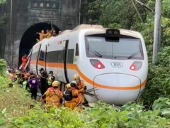 Rescue workers gather near one end of the train (Executive Yuan via AP)