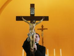 A priest holds a crucifix during a rehearsal in preparation for a Good Friday Mass (Brian Lawless/PA)