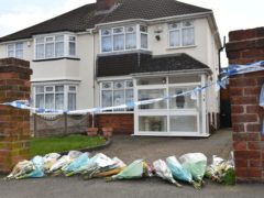 Flowers outside the house on Boundary Avenue in Rowley Regis, West Midlands, where a woman in her 80s died after being attacked by two escaped dogs (Jacob King/PA)