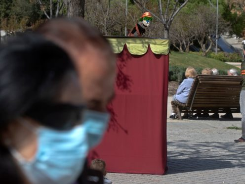 A couple wearing protective masks walk past a puppet show in a park in Madrid, Spain (Paul White/AP)