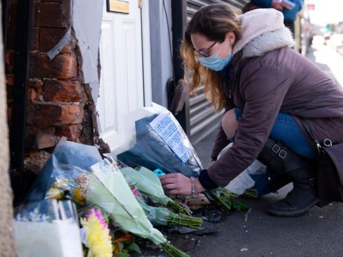 A woman lays flowers at the scene on High Street, Brownhills, near Walsall in the West Midlands, where a two-week-old baby boy in a pram was hit by a BMW car at around 4pm on Easter Sunday. West Midlands Police said the baby was rushed to hospital but nothing could be done to save him. Picture date: Monday April 5, 2021.