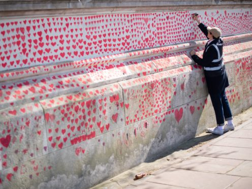 A volunteer adds hearts to the Covid-19 memorial wall in Westminster, central London (Dominic Lipinski/PA)