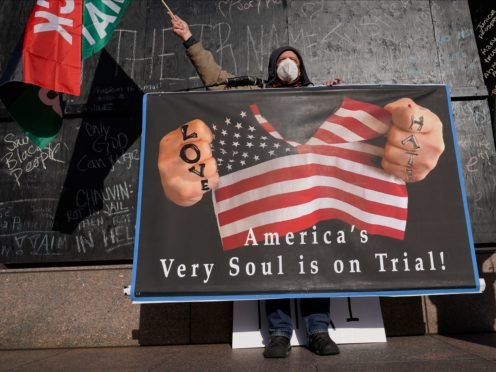 A protester holds a sign across the street from the Hennepin County Government Centre (Jim Mone/AP)