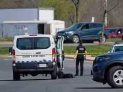 A crime scene technician stands near the scene of a shooting at a business park in Frederick, Maryland (Julio Cortez/AP)