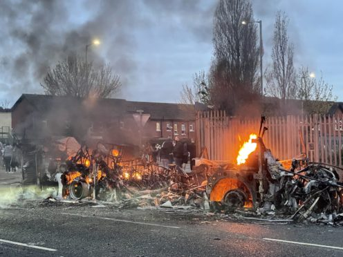 The wreckage of a Translink Metrobus on fire on the Shankill Road in Belfast (Liam McBurney/PA)