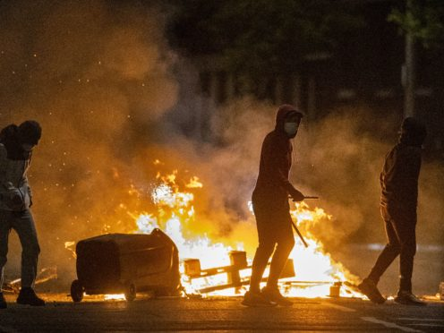 People stand next to a fire in a street in Belfast during further unrest. Picture date: Wednesday April 7, 2021.