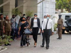 Mrs. World 2019 Caroline Jurie, center, leaves a police station after obtaining bail in Colombo, Sri Lanka, Thursday, April 8, 2021. Jurie's decision to remove the crown from the the winning Mrs. Sri Lanka contestant on stage moments after the winner was announced, because of claims she was a divorcee, drew widespread social media condemnation. The winner Pushpika de Silva who was crowned again later had complained to police that her head was wounded when the clips of her crown were removed by Jurie. (AP Photo/Eranga Jayawardena)