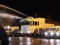 Objects are thrown towards PSNI officers an the water cannon on Springfield Road in Belfast (Liam McBurney/PA)